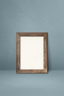 Wooden picture frame leaning on a grey wall. blank mockup template