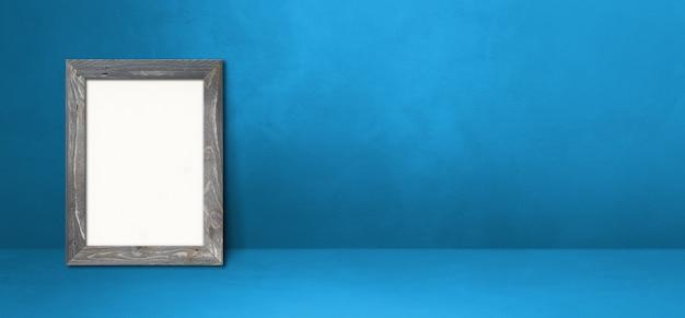파란색 벽에 기대어 나무 액자입니다. 빈 모형 템플릿입니다. 가로 배너
