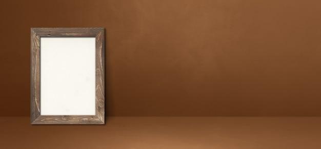갈색 벽에 기대어 나무 액자입니다. 빈 모형 템플릿입니다. 가로 배너