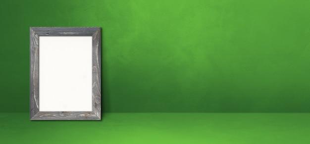 녹색 벽에 기대어 나무 액자입니다. 빈 모형 템플릿입니다. 가로 배너