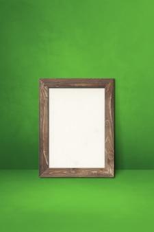 녹색 벽에 기대어 나무 액자입니다. 빈 모형 템플릿