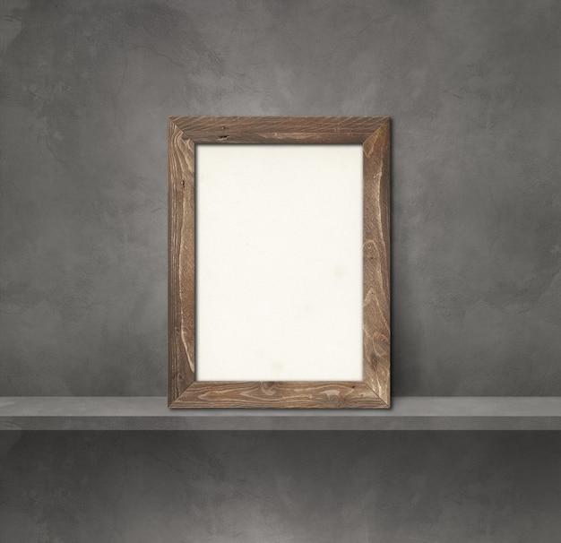 Деревянная рамка для фотографий, опирающаяся на серую полку. 3d иллюстрации. пустой шаблон макета. квадратный фон