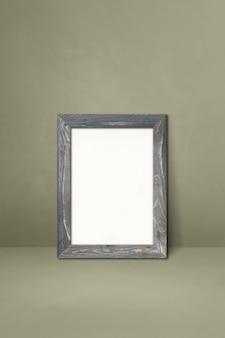 灰色の壁にもたれて木製の額縁。空白のモックアップテンプレート