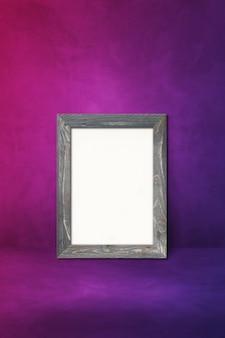 紫色の壁にもたれて木製の額縁。空白のモックアップテンプレート
