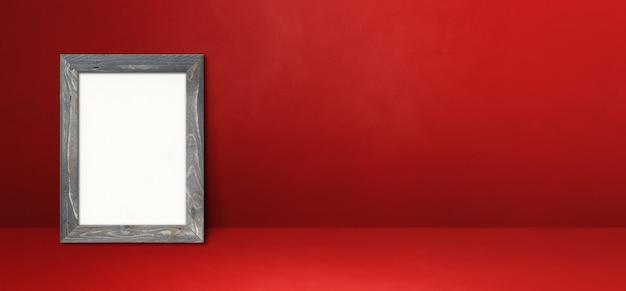 赤い壁に寄りかかって木製の額縁。空白のモックアップテンプレート。横バナー