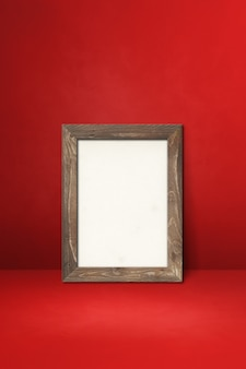 붉은 벽에 기대어 나무 액자입니다. 빈 모형 템플릿