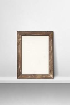 흰색 선반에 기대어 나무 액자입니다. 3d 그림입니다. 빈 모형 템플릿입니다. 세로 배경