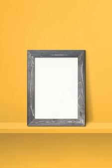 노란색 선반에 기대어 나무 액자입니다. 3d 그림입니다. 빈 모형 템플릿입니다. 세로 배경