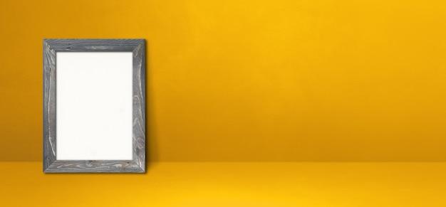 노란색 벽에 기대어 나무 액자입니다. 빈 모형 템플릿입니다. 가로 배너