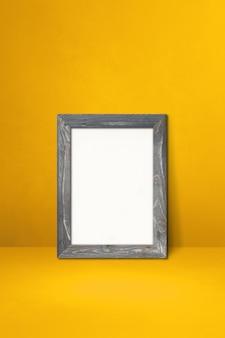 黄色の壁に寄りかかって木製の額縁。空白のモックアップテンプレート