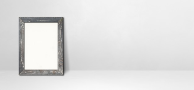 Wooden picture frame leaning on a white wall. blank mockup template. horizontal banner
