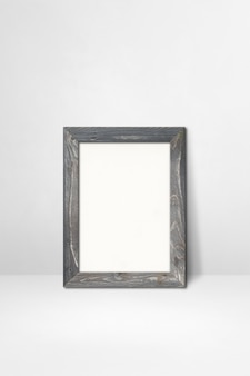 Wooden picture frame leaning on a white wall. blank mockup template
