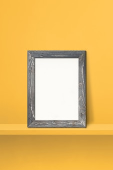 Wooden picture frame leaning on a yellow shelf. 3d illustration. blank mockup template. vertical background