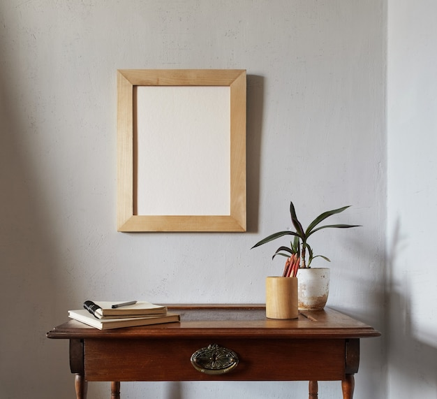 Wooden picture frame mockup. flowerpot on a pile of books on an old wooden desk. composition on a white wall surface