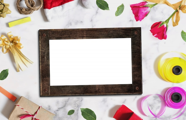 Wooden picture frame with christmas and valentines decorations on white concrete