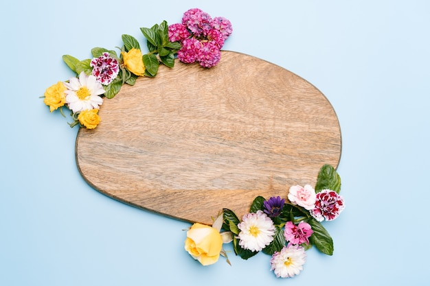 Wooden piece decorated with flowers on a pastel blue background. top view mockup with copy space.