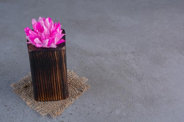 Un pezzo di legno di fiori viola in testa su un sacco.