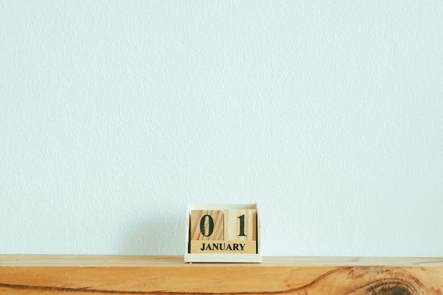 新年のコンセプトで白い壁にテキスト01januaryと木片。