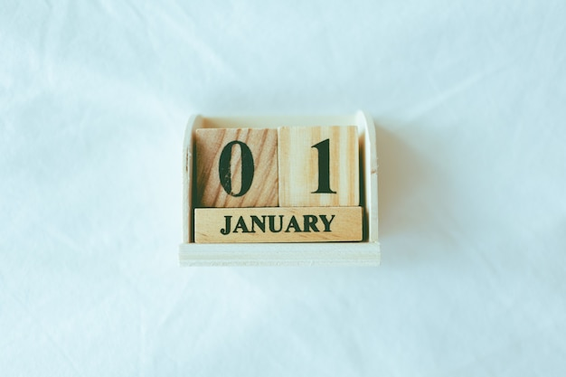Wooden pieces with text 01 january on white sheet.