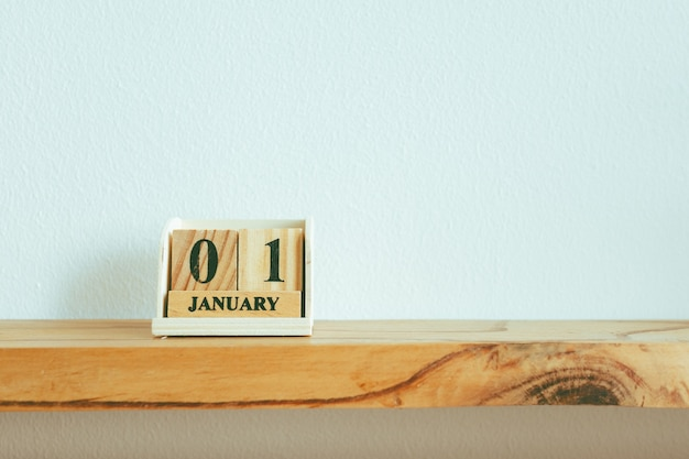 Wooden pieces with text 01 january on white wall in concept of new year.