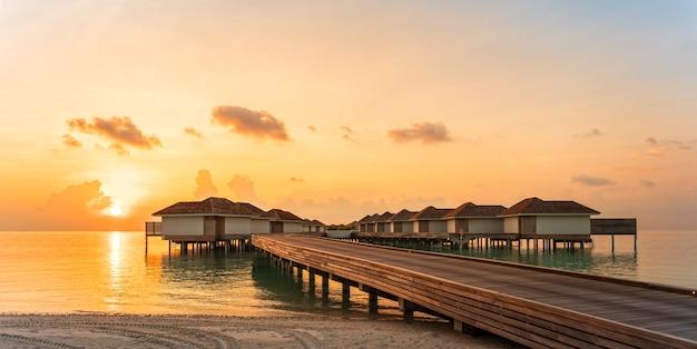 熱帯のビーチで日没時に木製の桟橋と水上ヴィラ