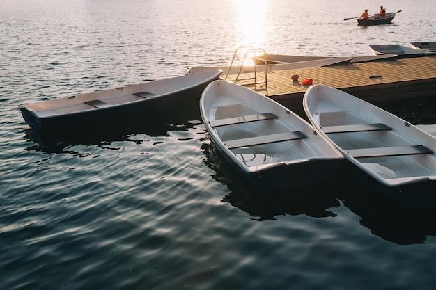 日の出の大きな湖の木製の桟橋とヨット
