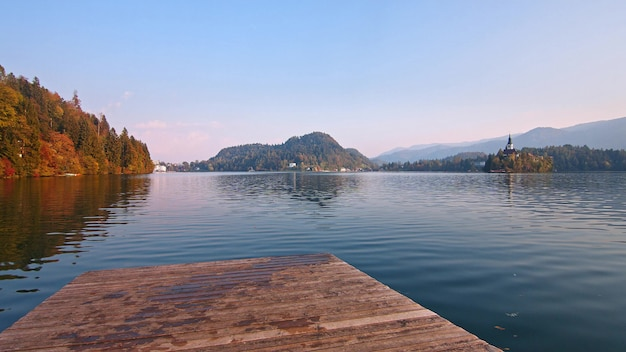 Wooden pier on the bled lake in slovenia with famous island and