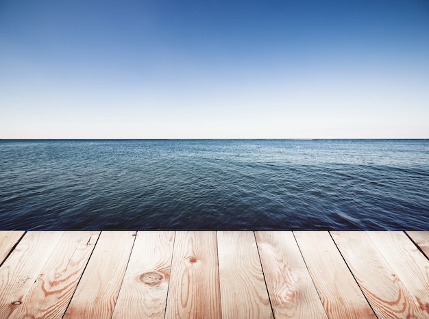 Wooden pier on blue sea and sky surface