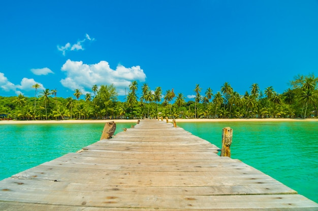 Wooden pier or bridge with tropical beach and sea in paradise island