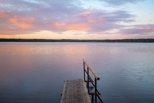 日の出の湖のそばにある木製の桟橋。