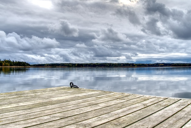 Деревянная пристань для небольших лодок с видом на пруд и красивое небо
