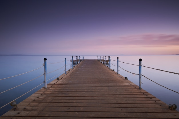 Wooden pier or jetty on sea sunset and sky reflection water. long exposure, dahab, egypt