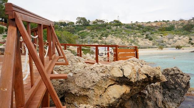 青い空の下の岩に囲まれた海の近くの木造の桟橋