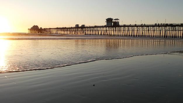 더미에 목조 부두, 일몰, 캘리포니아 미국, 오션 사이드 실루엣. 해질녘 맑은 바다 파도.