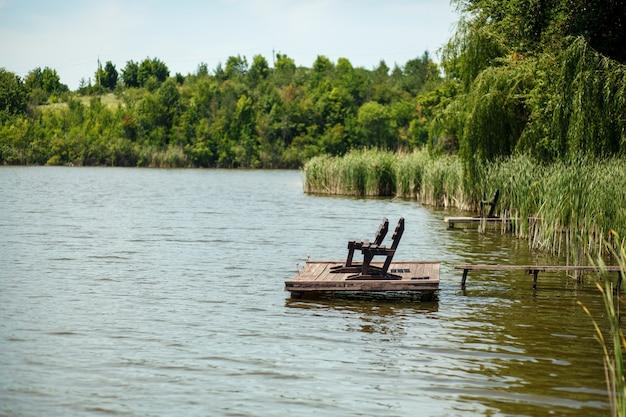 Деревянный пирс на озере в деревне. Premium Фотографии