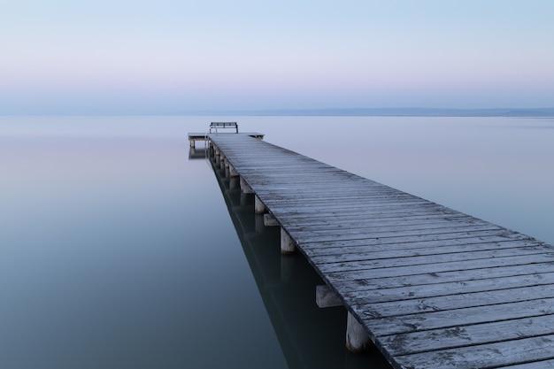 夕方には曇り空の下で海の上の木製の桟橋