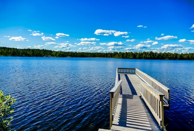 スウェーデンの背景に木々と青い空と美しい湖の上の木製の桟橋