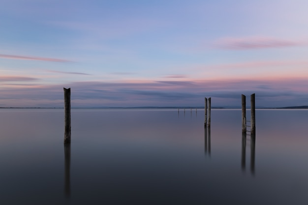 Wooden pier reflecting on the sea under the beautiful sunset sky
