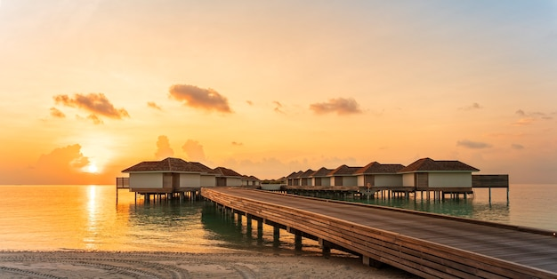 Wooden pier and water villas in sunset time by tropical beach