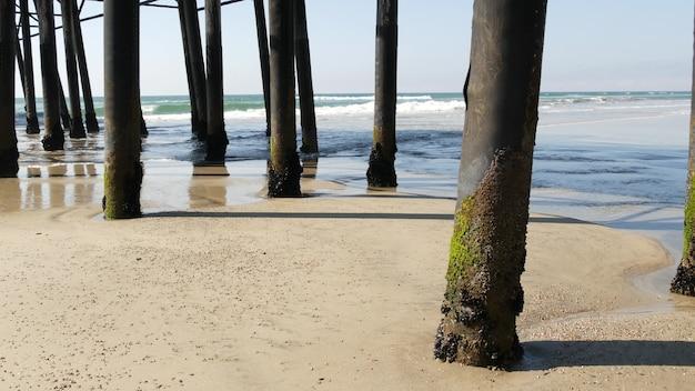 미국 캘리포니아주 오션사이드에 있는 오래된 부두, 판자 아래에 있는 나무 더미. 복고풍 빈티지 다리, 해안 산책로 아래의 말뚝, 철탑 또는 기둥. 파도, 바닷물 조수 및 모래 해변.