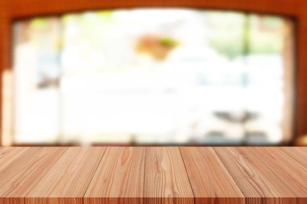 Деревянный сосновый стол сверху над размытым фоном, может использоваться для демонстрации монтажа продуктов или макета дизайна.