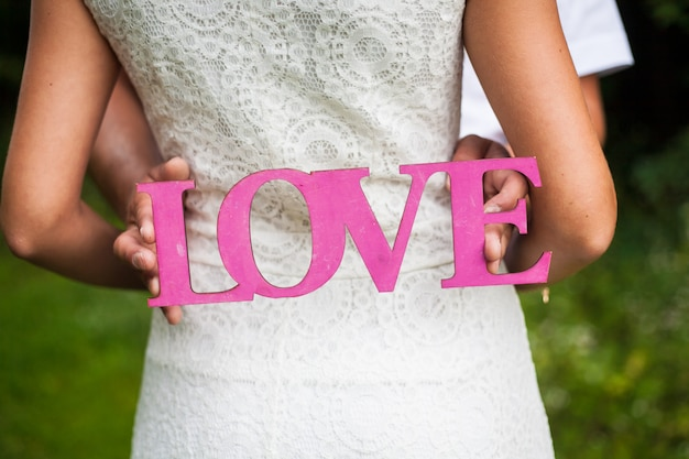 Wooden pink love letter in the hands of young