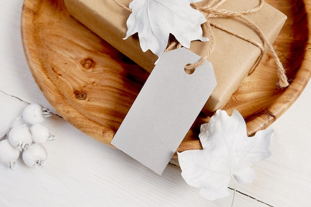 Wooden place with greeting gift and tag.