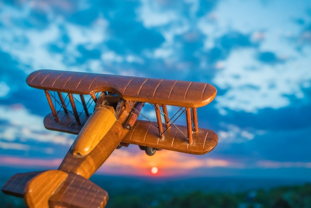 The wooden plane against the background of a sunset