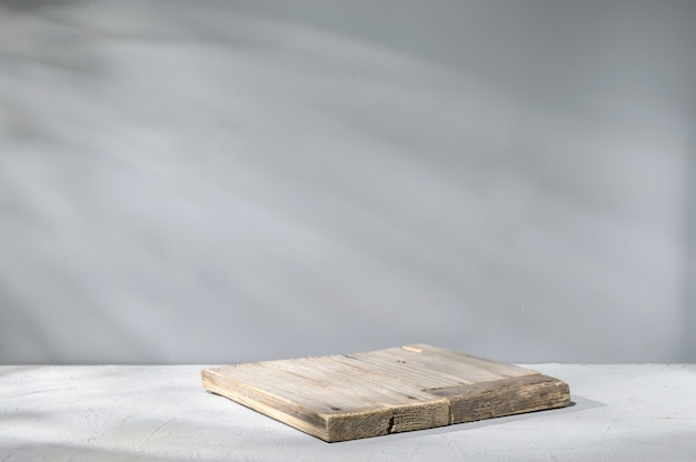 Wooden plank on gray surface with natural illumination