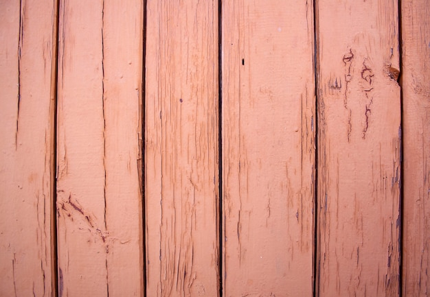 Wooden plank wall painted with brown paint. the paint is cracked and peeling.
