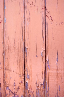 Wooden plank wall painted with reddish brown paint. the paint is cracked and peeling. background for design.