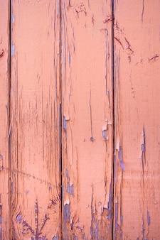 赤褐色のペンキで塗られた木の板の壁。塗装にひび割れや剥がれがあります。デザインの背景。