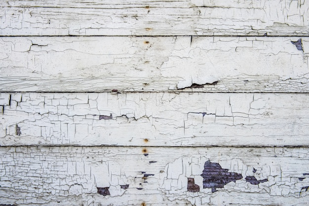 Wooden plank wall with cracked old white paint