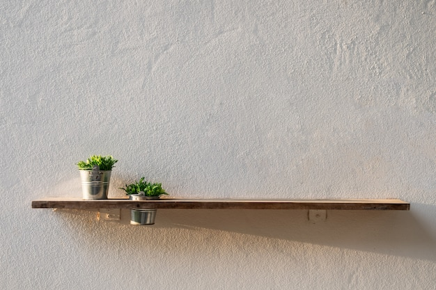 Wooden plank on wall with vase plant
